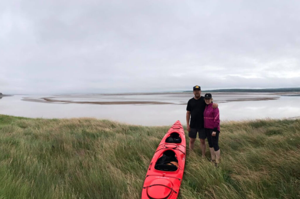 Kevin Anderson and Vallie Stearns stand beside their tandem kayak on the shores of the Maccan river in Nova Scotia. In the background are bay of Fundy tidal flats awaiting the tidal bore.