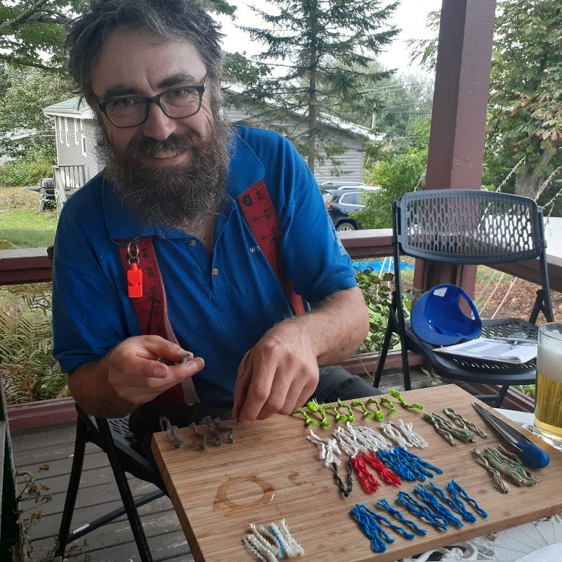 Bearded arborist John Haney is learning about the three kinds of arborist ropes on a lunch break on the front porch of Woodpecker Tree Care headquarters.