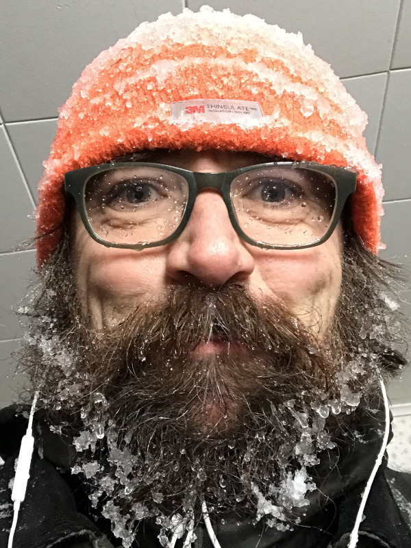 A bearded John Haney crusted in ice and snow and listening to headphones.