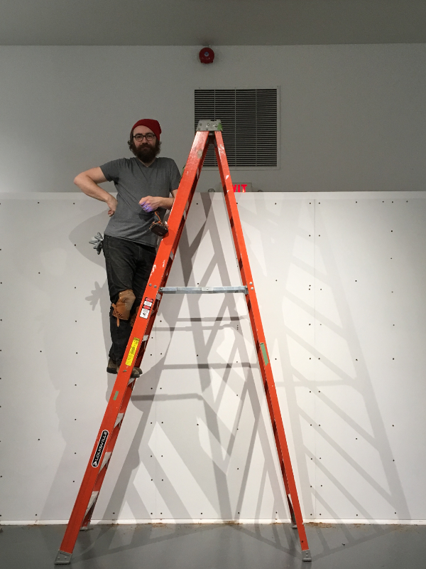 A gallery technician (John Haney) standing on a ladder while he hangs an exhibition for MFA students at Brock University.