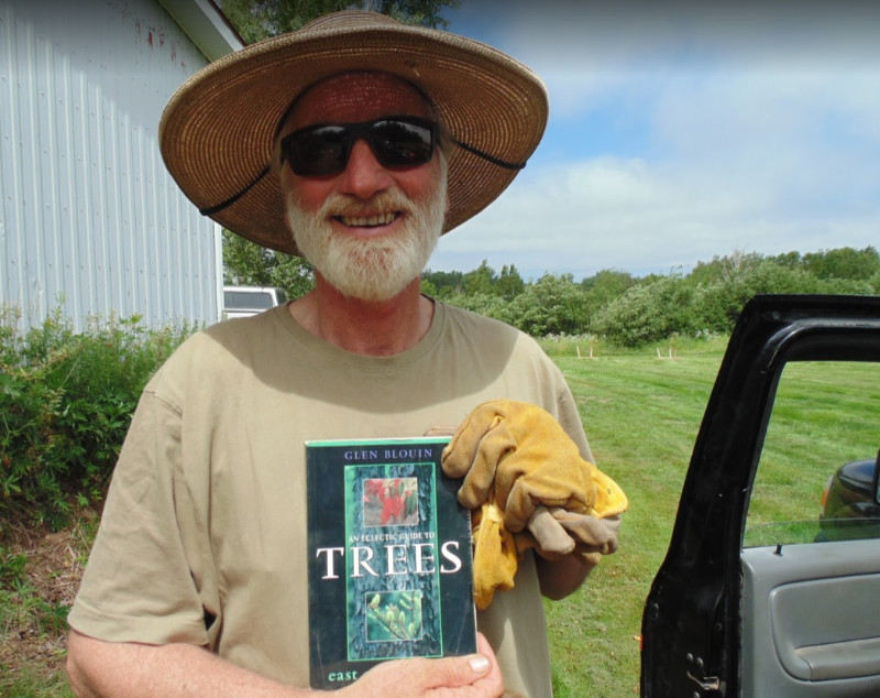 """Gardener Norm Hunter in hat and sunglasses shows off the book """"the eclectic guide to trees east of the rockies"""" by author Glen Blouin"""
