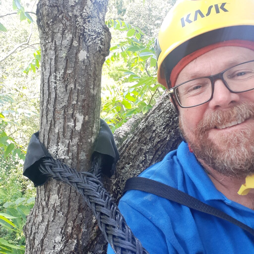 Kevin wears a hard hat and smiles next to a cable in a tree.