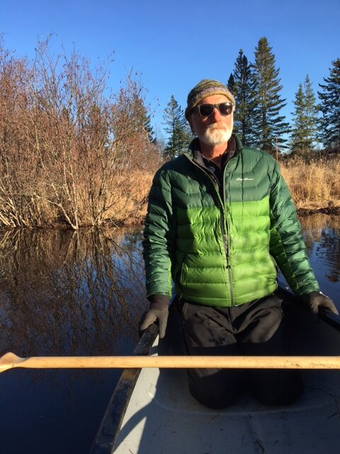 Norm Hunter sits in a kayak on still water.