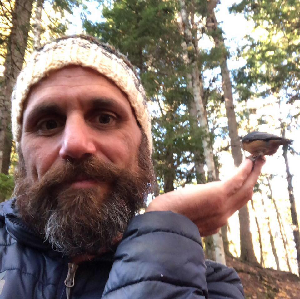 Luciano Onichino smiles while a small bird is perched on the fingers of his left hand. He is outdoors in the forest.