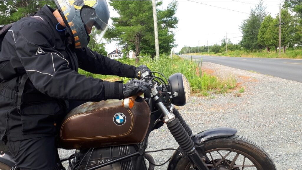 Luciano sits on a BMW motorcycle outdoors next to a round. He is wearing a helmet and gloves.
