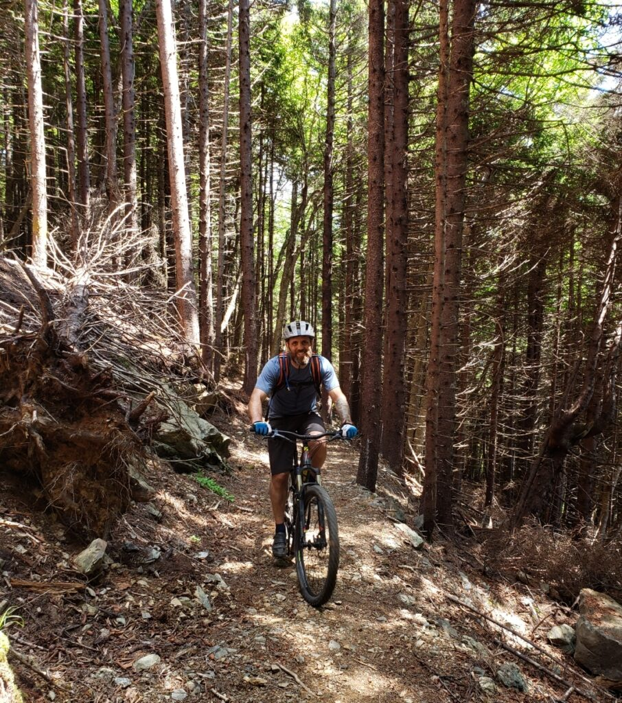 Luciano Onichino rides a bike in the forest.