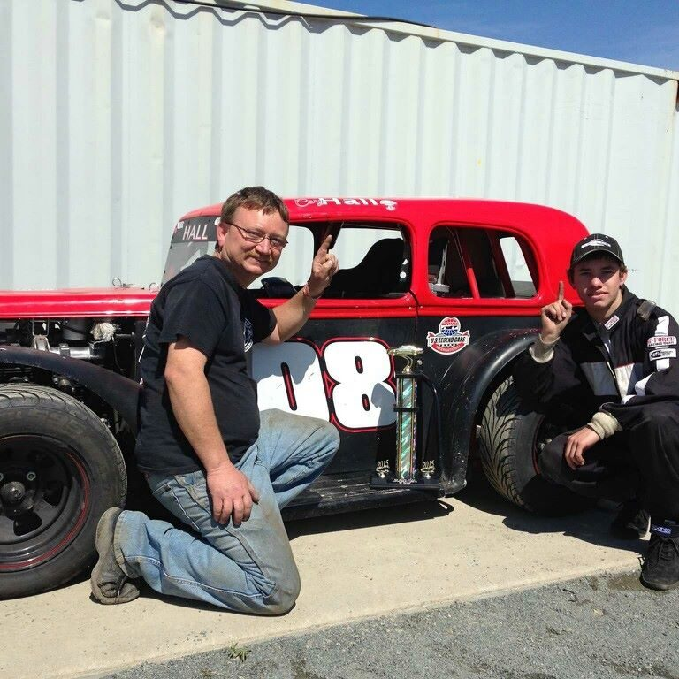 Scott Hall and his son Cory Hall kneel next to a winning racecar.