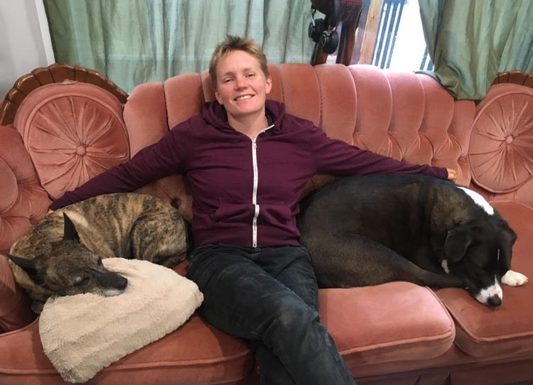 Becky sits on a couch with two dogs.