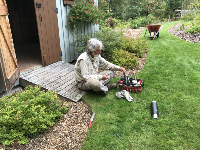 Norm sits crossed-legged on the ground in front of a garden shed. He is rifling through a tool pouch.